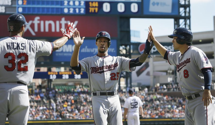 Minnesota Twins' Byron Buxton is congratulated by Aaron Hicks (32) and Kurt Suzuki (8) after scoring in the second inning of a baseball game against the Detroit Tigers, Sunday, Sept. 27, 2015 in Detroit. (AP Photo/Carlos Osorio)