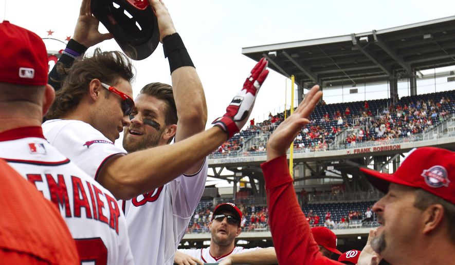 Washington Nationals' Matt den Dekker, left, has his batting helmet taken off by teammate Bryce Harper, center, as the team celebrates his home run in the second inning of a baseball game against the Philadelphia Phillies at Nationals Park, in Washington, Sunday, Sept. 27, 2015. (AP Photo/Jacquelyn Martin)