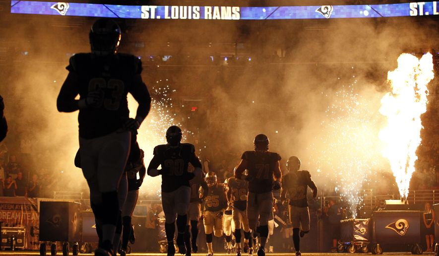 Members of the St. Louis Rams run on the field before an NFL football game against the Pittsburgh Steelers, Sunday, Sept. 27, 2015, in St. Louis. The game was delayed because part of the pyrotechnics used during the introductions briefly caught the turf on fire. (AP Photo/Billy Hurst)