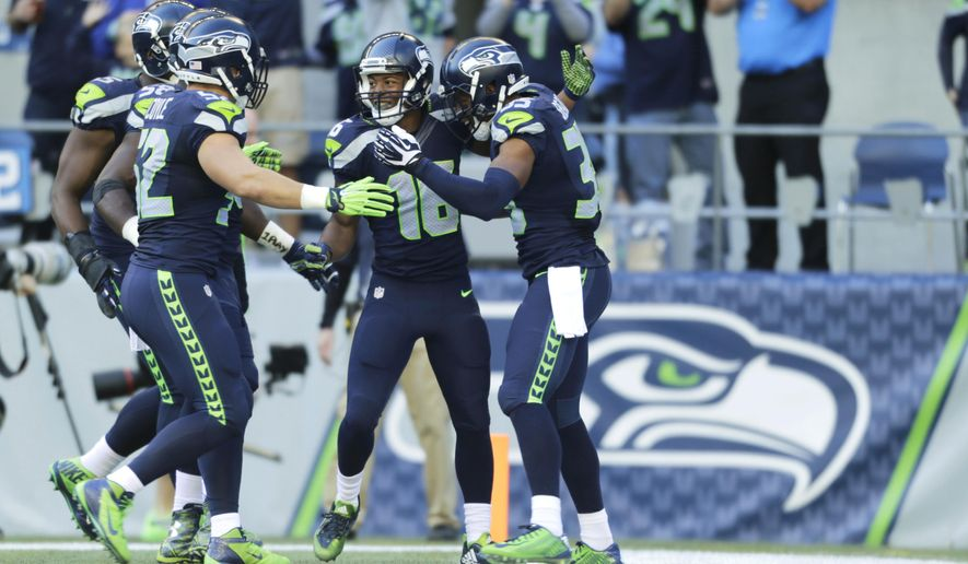 Seattle Seahawks wide receiver Tyler Lockett, second from right, is greeted by teammates, including DeShawn Shead, right, after returning a Chicago Bears kickoff 105 yards for a touchdown in the second half of an NFL football game, Sunday, Sept. 27, 2015, in Seattle. (AP Photo/John Froschauer)