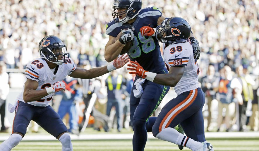 Seattle Seahawks tight end Jimmy Graham, center, gets through Chicago Bears free safety Adrian Amos, right, and cornerback Kyle Fuller, left, as he runs for a touchdown after a reception against the Chicago Bears in the second half of an NFL football game, Sunday, Sept. 27, 2015, in Seattle. (AP Photo/Elaine Thompson)