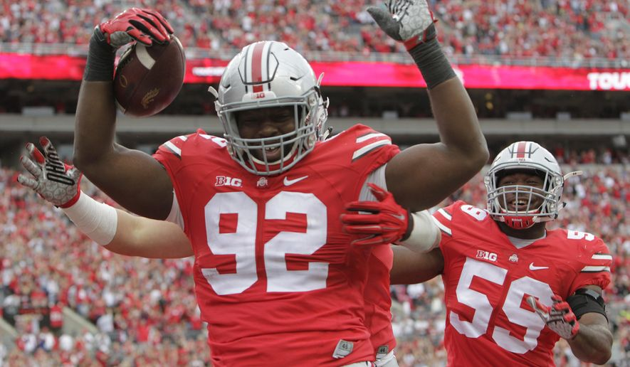 Ohio State defensive lineman Adolphus Washington, left, celebrates his touchdown against Western Michigan during the second quarter of an NCAA college football game, Saturday, Sept. 26, 2015, in Columbus, Ohio. (AP Photo/Jay LaPrete)