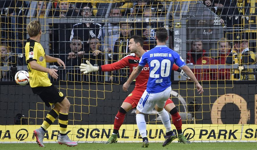 Darmstadt's Marcel Heller, right, scores the opening goal against Dortmund's goalkeeper Roman Buerki during the German Bundesliga soccer match between Borussia Dortmund and SV Darmstadt in Dortmund, Germany, Sunday, Sept. 27, 2015. (AP Photo/Martin Meissner)
