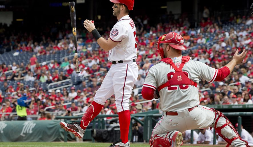 Washington Nationals' Bryce Harper (34) flips his bat in the air while batting in the first inning of a baseball game against the Philadelphia Phillies at Nationals Park, in Washington, on Sunday, Sept. 27, 2015, next to Phillies catcher Erik Kratz (28). (AP Photo/Jacquelyn Martin)