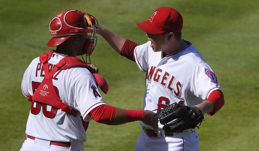 Los Angeles Angels' Carlos Perez, left, and relief pitcher Mike Morin congratulate each other after the Angels defeated the Seattle Mariners 3-2 in a baseball game, Sunday, Sept. 27, 2015, in Anaheim, Calif. (AP Photo/Mark J. Terrill)
