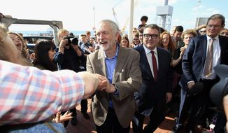 Labour party leader Jeremy Corbyn, centre,  is greeted by supporters and the party's deputy leader Tom Watson centre right, upon his arrival, prior to the start of the annual Labour party conference at the Brighton Centre, in Brighton, England, Saturday, Sept. 26, 2015. (Jonathan Brady/PA via AP) UNITED KINGDOM OUT