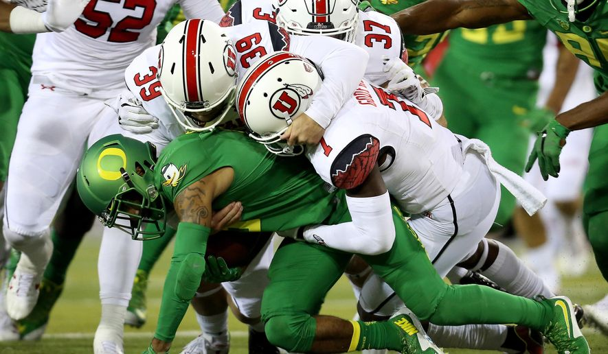 Oregon wide receiver Charles Nelson (6) is brought down by Utah defenders during the second half of an NCAA college football game, Saturday, Sept. 26, 2015, in Eugene, Ore. (AP Photo/Ryan Kang)