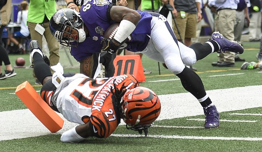 Baltimore Ravens wide receiver Steve Smith (89) dives over Cincinnati Bengals cornerback Dre Kirkpatrick (27) into the end zone for a touchdown during the second half of an NFL football game in Baltimore, Sunday, Sept. 27, 2015. (AP Photo/Nick Wass)