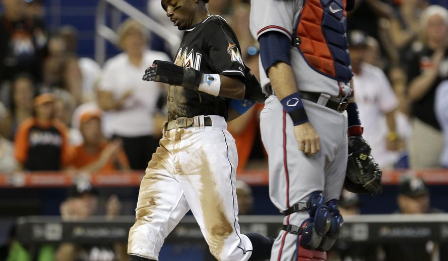 Miami Marlins' Dee Gordon, left, scores on a base hit by Martin Prado as Atlanta Braves catcher A.J. Pierzynski, right, looks on in the fifth inning of a baseball game, Sunday, Sept. 27, 2015, in Miami. Marlins' Miguel Rojas also scored on the hit. (AP Photo/Alan Diaz)