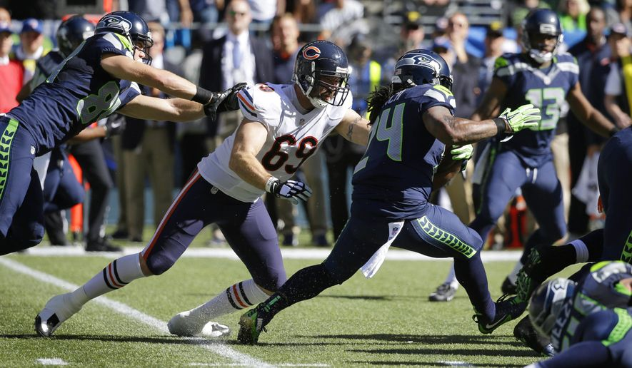 Seattle Seahawks running back Marshawn Lynch (24) runs the ball as Chicago Bears outside linebacker Jared Allen (69) reaches for a tackle attempt while being blocked by Seahawks' tight end Cooper Helfet, left, in the first half of an NFL football game, Sunday, Sept. 27, 2015, in Seattle. (AP Photo/Elaine Thompson)