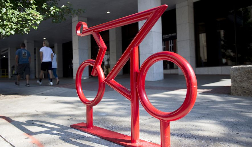 "This photo taken Sept. 19, 2015, shows one of four new public art pieces called ""Artful Bike Racks"", this one installed in front of Bank of the James building on Main Street in downtown Lynchburg, Va.   The project was coordinated by James River Council for the Arts and Humanities and aims to enhance interest in the arts. (Jill Nance/News & Daily Advance via AP) MANDATORY CREDIT"
