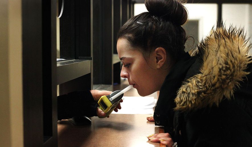 In this Sept. 21, 2015 photo, Autumn Regimbal, 19, blows into a Breathalyzer in the wing of the county jail dedicated to the state's 24/7 Sobriety Program in Sioux Falls, S.D. Regimbal is a participant in the state's nearly decade-old project that aims to reduce drunken driving and domestic violence by requiring offenders to prove twice a day that they have not been drinking. (AP Photo/Jay Pickthorn)