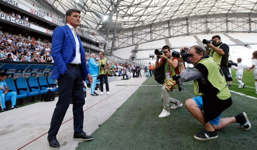 Marseille's Spanish coach Jose Miguel Gonzalez Martin Del Campo  know as Michel, at the beginning of the League One soccer match between Marseille and Angers, at the Velodrome Stadium, in Marseille, southern France, Sunday, Sept. 27, 2015. (AP Photo/Claude Paris)