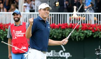 Jordan Spieth and his caddie Michael Greller react as he sinks his a putt on the 18th green to win the Tour Championship golf tournament at East Lake Golf Club, Sunday, Sept. 27, 2015, in Atlanta. (Curtis Compton/Atlanta-Journal Constitution via AP)