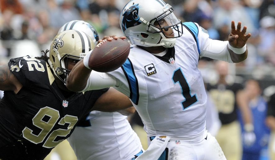 Carolina Panthers' Cam Newton (1) looks to pass under pressure from New Orleans Saints' John Jenkins (92) in the second half of an NFL football game in Charlotte, N.C., Sunday, Sept. 27, 2015. (AP Photo/Mike McCarn)