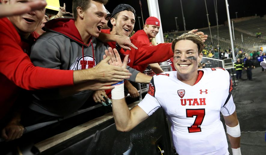 Utah quarterback Travis Wilson (7) high-fives the crowd after an NCAA college football game against Oregon, Saturday, Sept. 26, 2015, in Eugene, Ore. Utah won 62-20. (AP Photo/Ryan Kang)