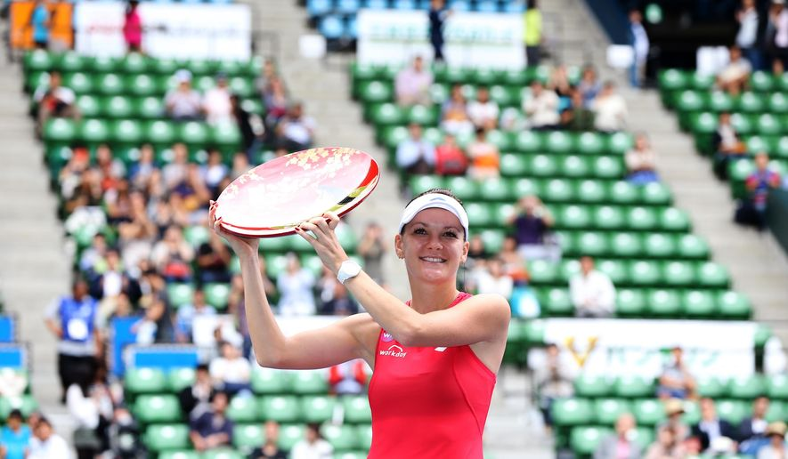 Agnieszka Radwanska of Poland holds the champion trophy to celebrate after defeating Belinda Bencic of Switzerland in their women's singles final at the Pan Pacific Open women?s tennis tournament in Tokyo, Sunday, Sept. 27, 2015. (AP Photo/Eugene Hoshiko)