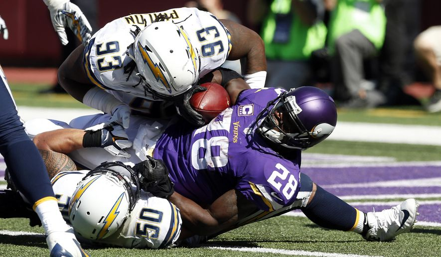 Minnesota Vikings running back Adrian Peterson (28) is hit by San Diego Chargers defensive end Darius Philon (93) and inside linebacker Manti Te'o (50) as he scores a touchdown in the first half of an NFL football game in Minneapolis, Sunday, Sept. 27, 2015. (AP Photo/Jim Mone)