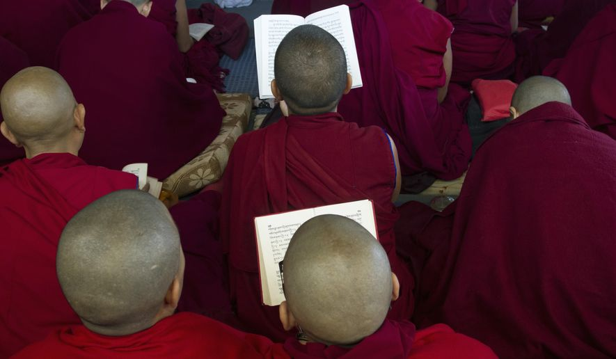 Exile Tibetan nuns pray at the Tsuglakhang temple in Dharmsala, the headquarters of the Tibetan government-in-exile, India, Saturday, Sept. 26, 2015. The Dalai Lama canceled his U.S. appearances for the month of October after doctors at Minnesota's Mayo Clinic advised him to rest, his office said Friday. (AP Photo/Ashwini Bhatia)