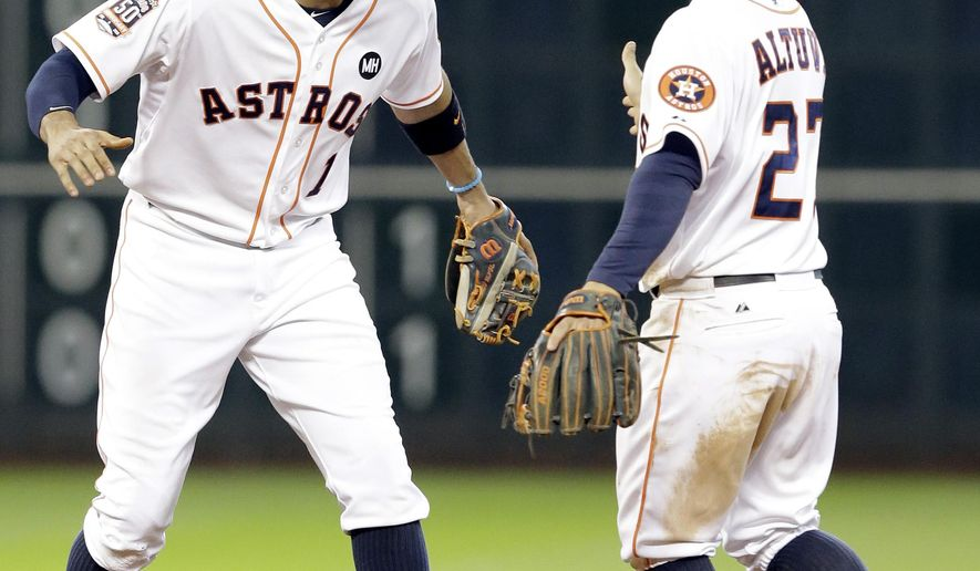 Houston Astros' Carlos Correa (1) and Jose Altuve (27) celebrate their 4-2 win over the Texas Rangers in a baseball game Sunday, Sept. 27, 2015, in Houston. (AP Photo/Pat Sullivan)