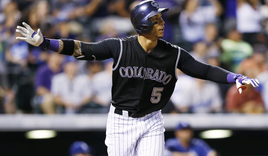 Colorado Rockies' Carlos Gonzalez follows the flight of his walkoff home run off Los Angeles Dodgers relief pitcher Yimi Garcia in the ninth inning of a baseball game Saturday, Sept. 26, 2015, in Denver. The Rockies won 8-6. (AP Photo/David Zalubowski)