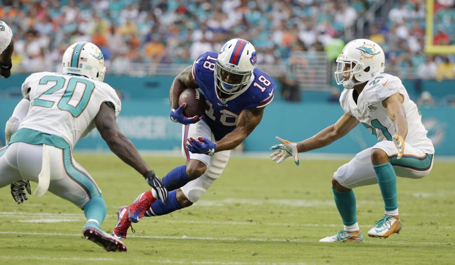 Buffalo Bills wide receiver Percy Harvin (18) runs the ball between Miami Dolphins strong safety Reshad Jones (20) and cornerback Brent Grimes (21) during the first half of an NFL football game, Sunday, Sept. 27, 2015, in Miami Gardens, Fla. Miko Grimes, the wife of Grimes, was arrested Sunday after Miami lost to the Buffalo Bills. According to a Miami-Dade Police news release, Grimes was arrested in the parking lot of Sunlife Stadium after the game. Miko Grimes is facing charges that include disorderly conduct, battery on a police officer and resisting arrest with violence. No details were given about what led to the arrest. (AP Photo/Wilfredo Lee)