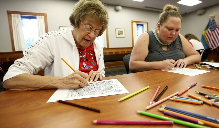 ADVANCE FOR USE SUNDAY, SEPT. 27 - In this photo taken Thursday, Sept. 10, 2015, Sandy Moses, left, and Holly Lawrence, both of Dubuque, Iowa, color at Carnegie-Stout Public Library during an Adult Coloring program in Dubuque, Iowa. (Nicki Kohl/Telegraph Herald via AP) MANDATORY CREDIT, MAGS OUT, TV OUT.