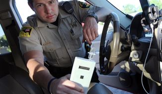 In this Sept. 21, 2015 photo, Minnehaha County Deputy Sheriff Elliott Crayne installs a car breathlyzer for a participant in the state's 24/7 Sobriety Program outside the county jail in Sioux Falls, S.D. Participants in the program are required to come to a test site every morning and evening to blow into a Breathalyzer. Those who live farther away have ignition interlock systems installed in their vehicles. (AP Photo/Jay Pickthorn)