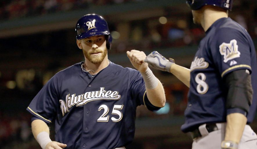 Milwaukee Brewers' Michael Reed, left, is congratulated by teammate Ryan Braun after scoring on a single by Jonathan Lucroy during the sixth inning of a baseball game against the St. Louis Cardinals on Saturday, Sept. 26, 2015, in St. Louis. (AP Photo/Jeff Roberson)