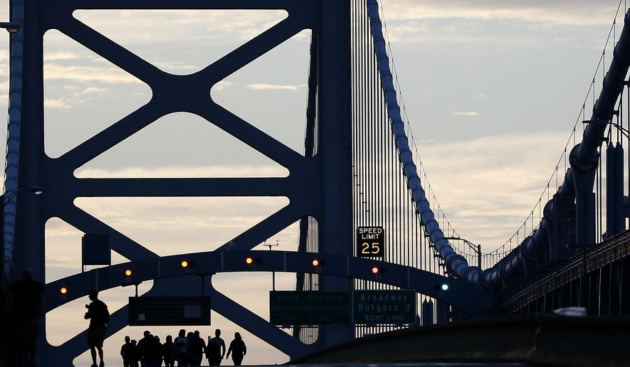 A family from Trenton, N.J., originally from Ecuador, walk over the Benjamin Franklin Bridge ahead of a Sunday Mass to be delivered by Pope Francis, Sunday, Sept. 27, 2015, in Philadelphia. Pope Francis celebrates a climactic outdoor Mass on the Benjamin Franklin Parkway Sunday before flying back to Rome. (AP Photo/Julio Cortez)