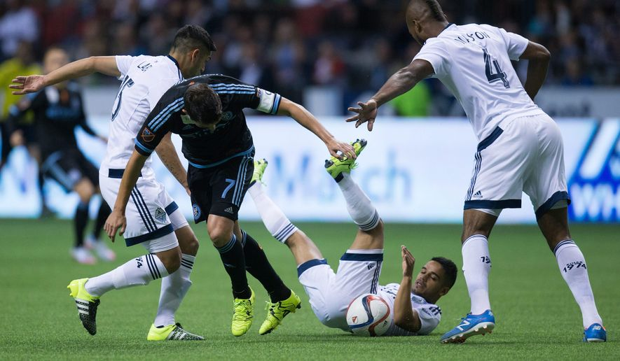Vancouver Whitecaps' Cristian Techara tumbles to the ground as he takes the ball away from New York City FC's David Villa, second from left, of Spain, as Whitecaps' Matias Laba, left, of Argentina, and Kendall Waston, of Costa Rica, defend during the first half of an MLS soccer match in Vancouver, British Columbia, on Saturday, Sept. 26, 2015. (Darryl Dyck/The Canadian Press via AP)