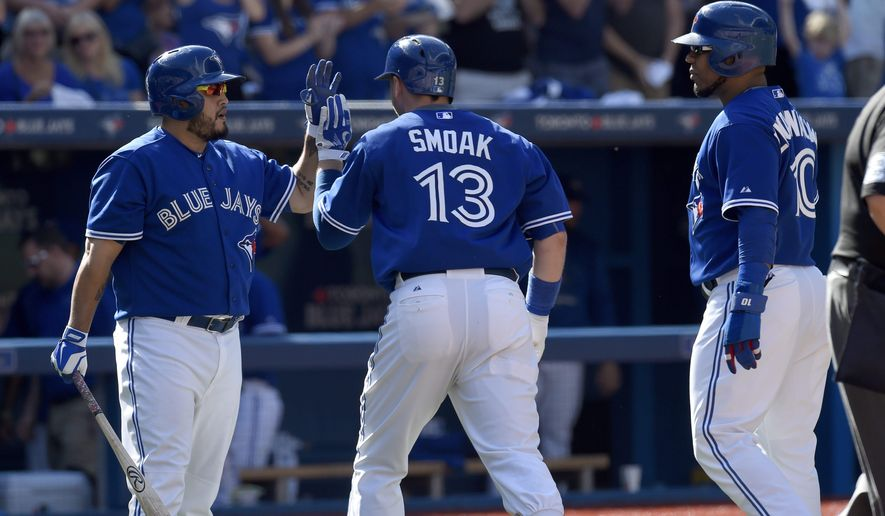 Toronto Blue Jays' Justin Smoak, center, celebrates his two-run home run with Dioner Navarro as Edwin Encarnacion looks on during sixth inning of a baseball game in Toronto, Sunday, Sept. 27, 2015. (Frank Gunn/The Canadian Press via AP) MANDATORY CREDIT