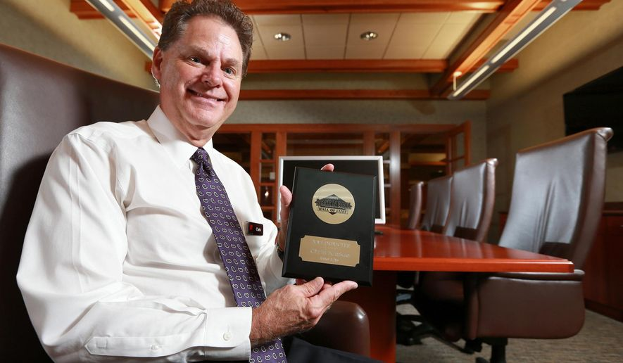 ADVANCE FOR USE SUNDAY, SEPT. 27 - In this photo taken Sept. 18, 2015, Home Federal vice president of consumer lending Chris Kaskie, who was recently inducted into the Iowa Rock 'n' Roll Music Association Hall of Fame as a member of the popular Iowa rock band Inner Lite, poses for a photo in the board room at Home Federal Bank in Grand Island. Neb. Still singing, Kaskie can be heard performing with the Trinity United Methodist Cross Point contemporary worship band in Grand Island. (Barrett Stinson/The Independent via AP) MANDATORY CREDIT, TV OUT, RADIO OUT, MAGAZINES OUT.