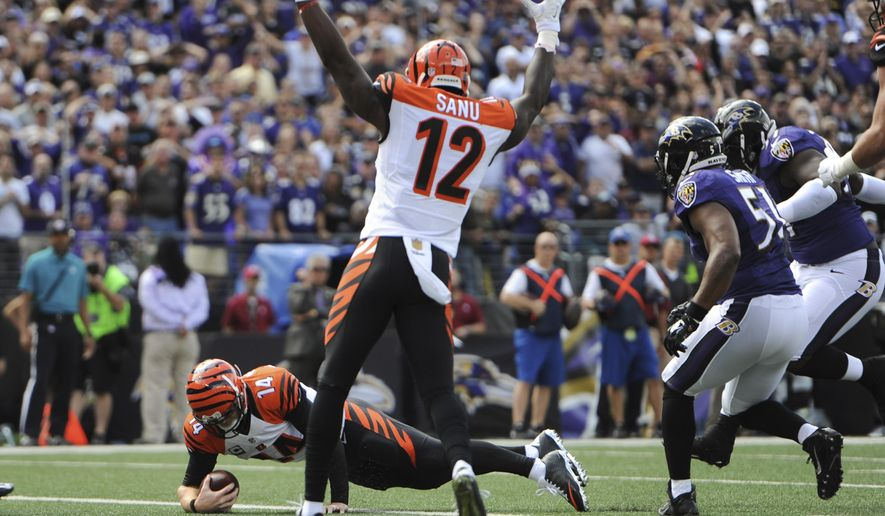 Cincinnati Bengals wide receiver Mohamed Sanu (12) signals a touchdown as quarterback Andy Dalton (14) dives into the end zone for a touchdown during the first half of an NFL football game against the Baltimore Ravens in Baltimore, Sunday, Sept. 27, 2015. (AP Photo/Gail Burton)