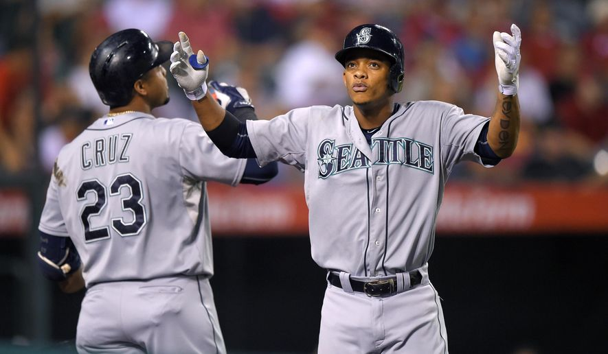 Seattle Mariners' Ketel Marte, right, celebrates with Nelson Cruz after hitting a solo home run during the third inning of a baseball game against the Los Angeles Angels, Saturday, Sept. 26, 2015, in Anaheim, Calif. (AP Photo/Mark J. Terrill)
