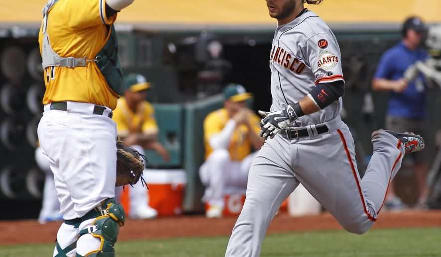 San Francisco Giants' Brandon Crawford, right, scores past Oakland Athletics catcher Stephen Vogt during the second inning of a baseball game, Sunday, Sept. 27, 2015, in Oakland, Calif. (AP Photo/George Nikitin)