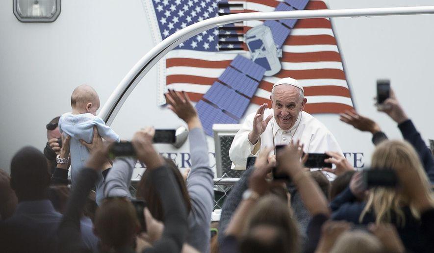 Pope Francis arrives for a Mass on the Benjamin Franklin Parkway, Sunday, Sept. 27, 2015, in Philadelphia. (AP Photo/Alessandra Tarantino)