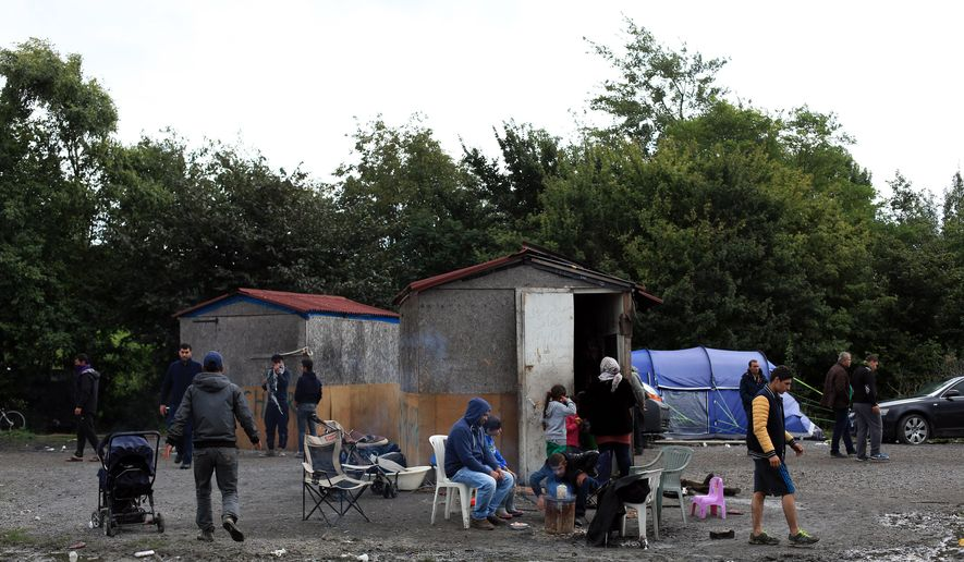 In this photo taken Friday, Sept. 18, 2015, migrants from Syria wait in the migrant camp of Grande Synthe, before an attempt to get to Britain, outside Dunkirk, northern France. Migrants in Teteghem or nearby Grande-Synthe wait eagerly for the service they signed up for. People smugglers who get rich off desperate migrants span the globe, and their tentacles extend into nooks and crannies like Teteghem, a small town outside Dunkirk. Here the smuggling kingpins are firmly in control, and growing nasty. (AP Photo/Thibault Camus)