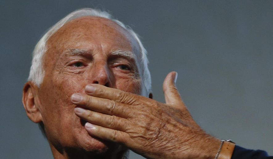 Italian fashion designer Giorgio Armani blows a kiss during the presentation of the book 'Giorgio Armani' written by journalist Suzy Menkes, at the end of unveiling of his women's Spring-Summer 2016 collection, part of the Milan Fashion Week, in Milan, Italy, Monday, Sept. 28, 2015. (AP Photo/Luca Bruno)