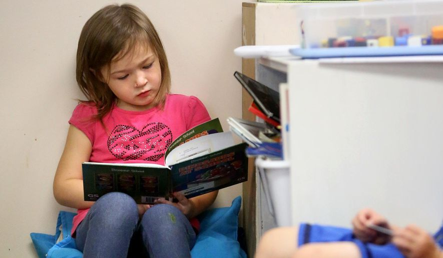 In a Tuesday, Sept. 22, 2015 photo, preschooler Claire Splinter reads at Mercy Child Development Center and Preschool in Dubuque, Iowa. Preschool is becoming a more popular option for families with young children across Iowa. (Jessica Reilly/Telegraph Herald via AP) MANDATORY CREDIT