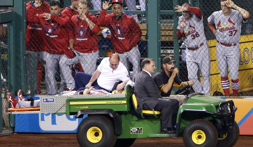 St. Louis Cardinals left fielder Stephen Piscotty is driven past the Cardinals bullpen after colliding with center fielder Peter Bourjos going after a fly ball by Pittsburgh Pirates' Josh Harrison in the seventh inning of a baseball game in Pittsburgh, Monday, Sept. 28, 2015. Bourios made the catch for the out. (AP Photo/Gene J. Puskar)