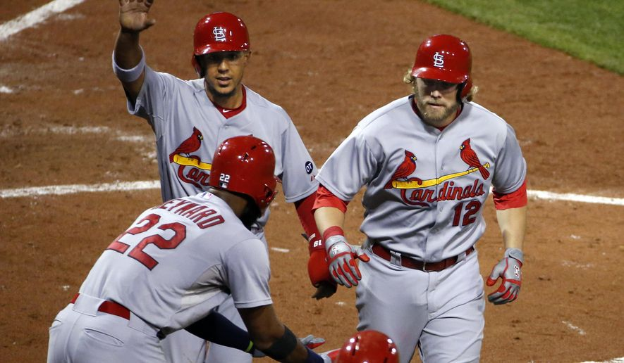St. Louis Cardinals' Mark Reynolds (12) celebrates with teammates Jon Jay, left rear, and Jason Heyward (22) after hitting a pinch hit two-run home run off Pittsburgh Pirates relief pitcher Mark Melancon in the ninth inning of a baseball game in Pittsburgh, Monday, Sept. 28, 2015. (AP Photo/Gene J. Puskar)
