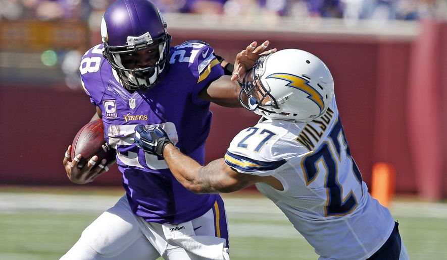 Minnesota Vikings running back Adrian Peterson (28) pushes off the tackle of San Diego Chargers strong safety Jimmy Wilson (27) on his way to a touchdown in the second half of an NFL football game in Minneapolis, Sunday, Sept. 27, 2015. (AP Photo/Jim Mone)