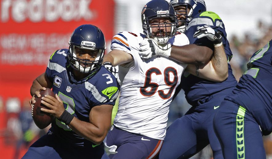 Seattle Seahawks quarterback Russell Wilson (3) looks to pass as Chicago Bears outside linebacker Jared Allen (69) is blocked by Seahawks' tackle Russell Okung, right, in the first half of an NFL football game, Sunday, Sept. 27, 2015, in Seattle. (AP Photo/Elaine Thompson)