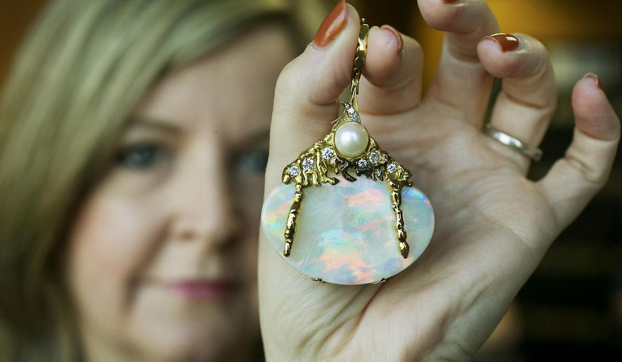 In this Sept. 25, 2015 photo, Georgia Sanchez, Assistant Treasurer with the City of Austin, holds an opal, given to the city from it's sister city Adelaide, South Australia back in July 1983, in Austin, Texas. Now, more than three decades later, the Adelaide City Council is asking for the return of the opal, a gemstone that was once worn with pride by Austin mayors' wives but that a city spokesman says has been sitting in a safety deposit box since the late 1990s. (Ralph Barrera/Austin American-Statesman via AP)  AUSTIN CHRONICLE OUT, COMMUNITY IMPACT OUT, INTERNET AND TV MUST CREDIT PHOTOGRAPHER AND STATESMAN.COM, MAGS OUT; MANDATORY CREDIT