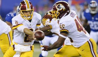 Washington Redskins quarterback Kirk Cousins (8) hands the ball to Alfred Morris (46) during the first half an NFL football game Thursday, Sept. 24, 2015, in East Rutherford, N.J. (AP Photo/Bill Kostroun)