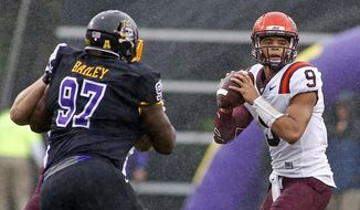 Virginia Tech's Brenden Motley (9) looks to pass the ball as he is hurried by East Carolina's Damage Bailey (97) during the first half of an NCAA college football game in Greenville, N.C., Saturday, Sept. 26, 2015. East Carolina won 35-28. (AP Photo/Karl B DeBlaker)