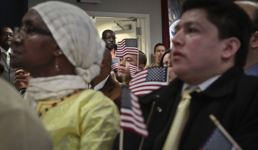 Immigrants hold miniature U.S. flags as they listen to a video broadcast from President Barack Obama during a naturalization ceremony attended by Mayor Michael Bloomberg in New York, in this Dec. 18, 2013, file photo. (AP Photo/Bebeto Matthews, File)