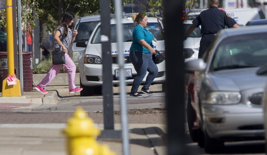 Employees are led out of Crusader Community Health clinic by police after reports of an armed man Monday, Sept. 28, 2015, in Rockford, Ill. The standoff between the man the police ended peacefully and Rockford Deputy Police Chief Pat Hoey says the suspect was taken into custody after a nearly four-hour standoff. (Max Gersh/Rockford Register Star via AP)  MANDATORY CREDIT