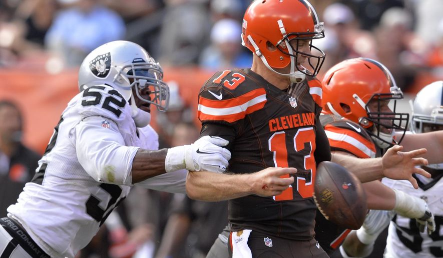 Oakland Raiders defensive end Khalil Mack (52) hits Cleveland Browns quarterback Josh McCown (13) causing a fumble in the second half of an NFL football game, Sunday, Sept. 27, 2015, in Cleveland. The Raiders recovered the fumble. (AP Photo/David Richard)